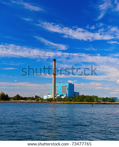 Power station by the edge of the ocean with blue sky