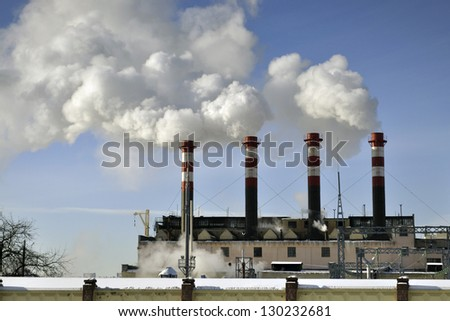 power station chimneys over blue sky background - stock photo