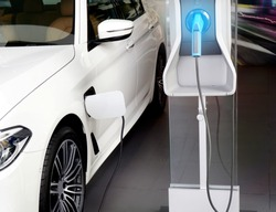 Power supply connect to electric car for add charge to the battery. Charging re technology industry transport which are the future of the Automobile.