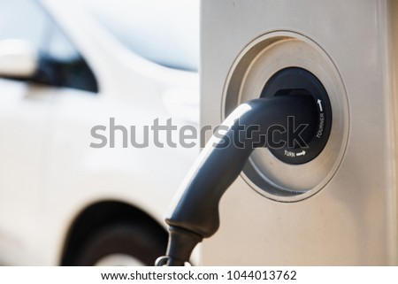 Power supply for electric car charging. Close up of the car charging station socket. White automobile being charged on bright sunny day. #1044013762