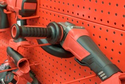 Power tools on display stand. Colors - red, black. Angle grinder close-up. Power tool shop concept. Selective focus.
