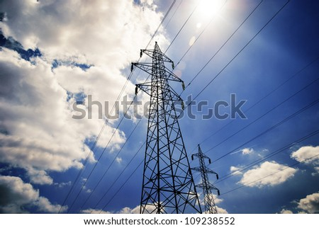 Power towers with blue sky and clouds