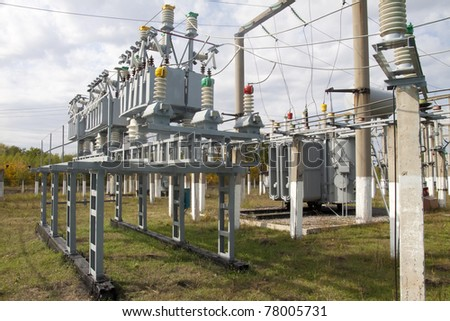 Power transformer in a distribution substation separated from another one by a wall.