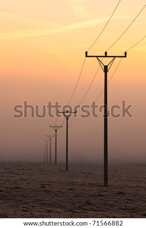 Power-transmission pole in the mist in winter nature