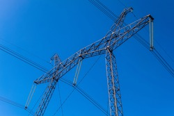 Power Transmission Tower. Air hi-voltage electric line supports on a blue sky background. Electricity garlands and insulators with electric wires on a top steel mast support.