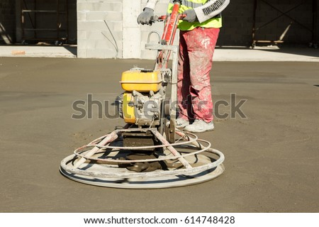 Power troweling fresh concrete surface on a construction site. Power trowel concrete finishing machine working. Shallow depth of field