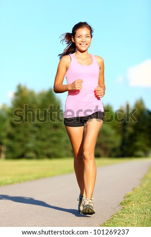 Power walking woman training in park. Beautiful sporty fitness model during outdoor workout. Mixed race Asian Chinese / Caucasian girl.