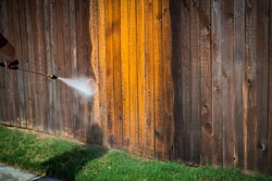 Power washing wooden fence to restore it to new. Restoration High pressure power washer spraying and cleaning wooden fence. Make old turn new. Dirty fence turned brand new again. grass and sidewalk