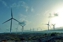 power wind turbines at sunset