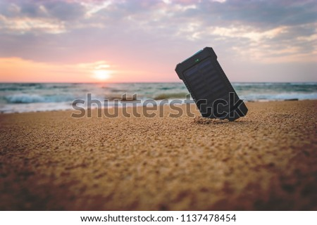 Powerbank in the sand on the background of the rising sun in the cloudy sky and the blue sea. Alternative energy source. battery is charged by solar energy. on desert island. beach #1137478454