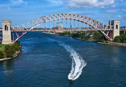 Powerboat leaves a wake as it drives under the Hell Gate Bridge, in the East River, New York, NY. The railroad Bridge connects Wards and Randalls Island to Queens and servers Amtrak railroad.