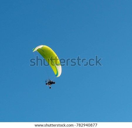 Powered paragliding in the blue sky. #782940877