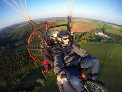 Powered paragliding tandem flight, man taking selfie with action camera