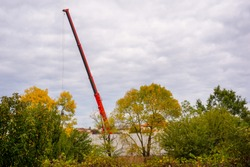 Powerful and huge telescopic arm of a mobile crane truck, hidden among leafy trees, lifting a load by means of cables to set up a prefabricated wall on a construction site