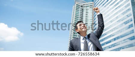 Powerful Asian businessman displaying victory, empowering himself, outside the office with skyscrapers in the background, panoramic banner with copy space