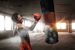 Powerful asian male boxer with punching bag for uppercut training
