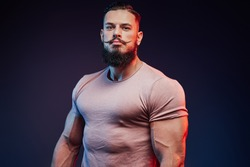 Powerful athlete with black beard and mustache posing in casual clothing in dark background.