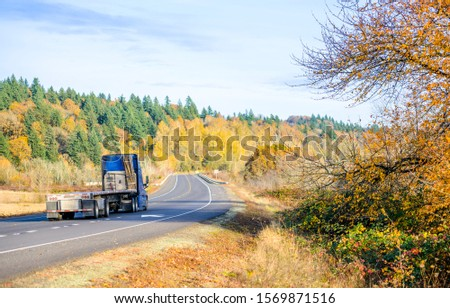 Powerful Big classic American bonnet rig blue semi truck with high cab transporting empty flat bed semi trailer running on the autumn road with forest on the hill going to warehouse for load cargo #1569871516
