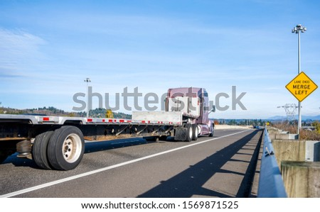 Powerful Big classic American bonnet rig brown semi truck with high cab transporting empty flat bed semi trailer running on the straight road with protection fence going to warehouse for load cargo #1569871525