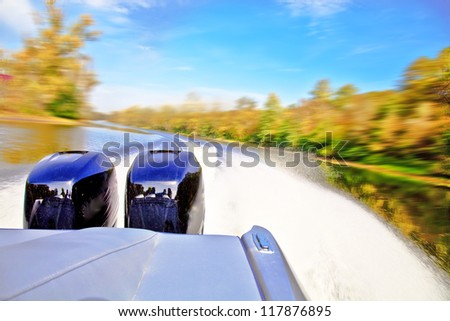Powerful boat racing at fast speed on the river. Motion blur. View of the stern and two powerful outboard engines. - stock photo