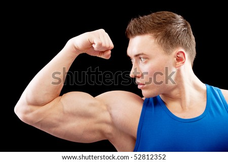 Powerful body builder shows biceps, isolated on black background.