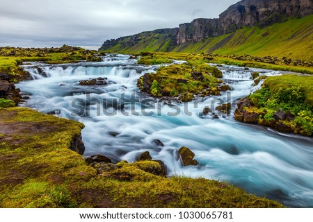 Powerful cascading waterfalls. Travel in Iceland. Wide picturesque valley along highway number one around the island. Concept of active and extreme tourism