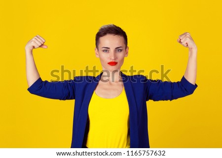 Stock Photo Powerful confident woman flexing her muscles isolated on yellow wall background. Neutral human face expressions, emotions. Beautiful woman in blue suit, yellow shirt with short hair and red lipstick