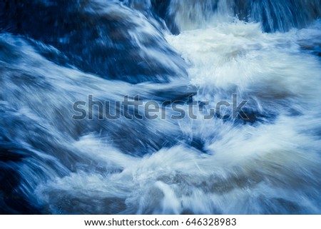 Powerful currents of river water converge in violent splashes.