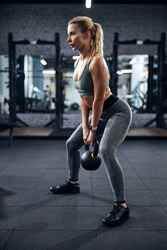 Powerful female bending her knees and returning her body to an upright position with a heavy kettlebell