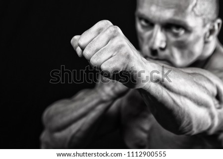 Powerful fighter in front of black background	  #1112900555