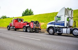 Powerful heavy-duty big rig mobile tow semi truck with emergency lights and towing equipment prepare to tow broken white big rig semi tractor standing out of service on the road side