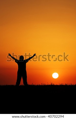 Powerful image of a person in silhouette worshiping a beautiful sunset