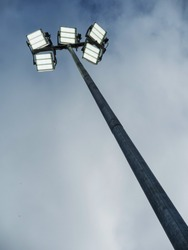 Powerful LED light on a metal pole turned on, cloudy sky background. Concept sport event, game.