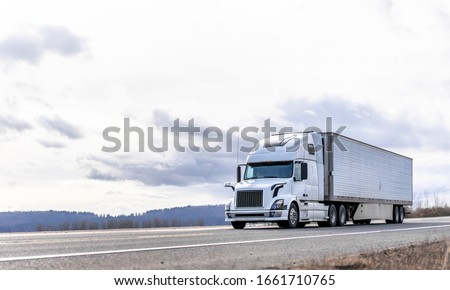 Powerful long haul big rig industrial grade diesel semi truck transporting commercial food cargo in refrigerated semi trailer running on the flat road with sky and hills view in Columbia Gorge Сток-фото ©