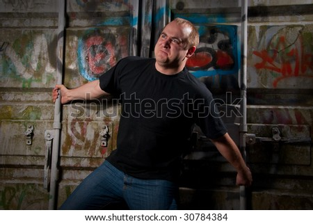 Powerful man expression portrait in a dark near container with graffiti