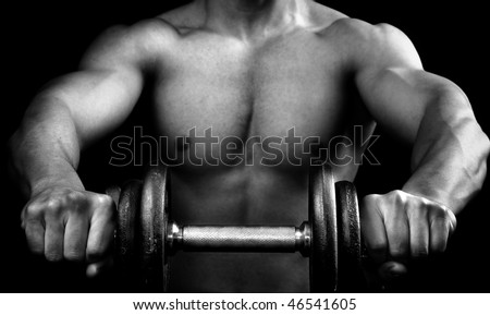 Powerful muscular guy holding a dumbbell