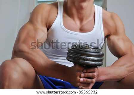 Powerful muscular man lifting weight - stock photo