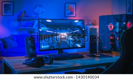 Powerful Personal Computer Gamer Rig with First-Person Shooter Game on Screen. Monitor Stands on the Table at Home. Cozy Room with Modern Design is Lit with Blue and Neon Light. #1430140034