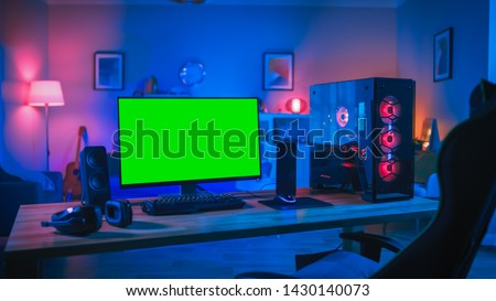 Powerful Personal Computer Gamer Rig with Mock Up Green Screen Monitor Stands on the Table at Home. Cozy Room with Modern Design is Lit with Pink Neon Light. #1430140073