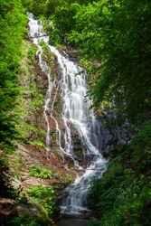 Powerful Pilj waterfall on Old mountain (Stara planina) in Serbia, cascading down the wet, red rocks and surrounded by vivid green trees