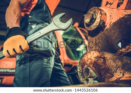Powerful Professional Mechanic. Heavy Duty Equipment Maintenance. Industrial Concept. Caucasian Men with Large Iron Wrench in a Hand. #1443526106