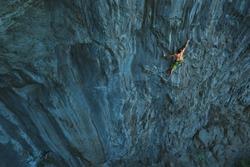 Powerful Rock climber climbing on a big rock wall