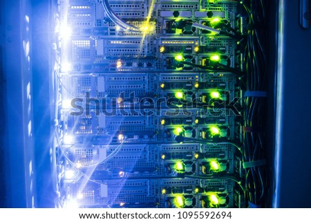 Powerful server hardware works in a dark server room. Technical hosting site of a large Internet provider.Modern high-speed Internet connection of network interfaces #1095592694