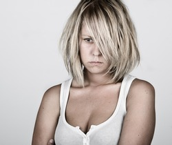 Powerful Shot of a Pensive Blonde Female in White Vest against Grey Background