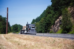 Powerful spectacular professional commercial classic dark blue semi - truck with an open trailer flat bed and chrome accents transports building boards on the highway near the picturesque cliffs.