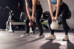 Powerful sportive people lifting up a heavy kettle ball in a gym, body building exercise. Body building workout in an indoor gym. Asian sportive people making a muscular and bodybuilding training.