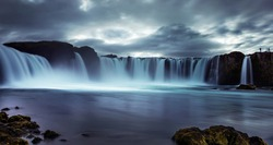 Powerful streams of the waterfall cascading into the reservoir. Dramatic sky. Long exposure. Godafoss waterfall, Iceland.