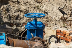 Powerful system for shutting off the main pipeline water after repair work. Pipes and valves. Blue crane in the open ground. Installation of the gate valves for city groundwater system.