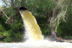 Powerful water flowing from a large pipe using a water pump for agricultural use in paddy fields