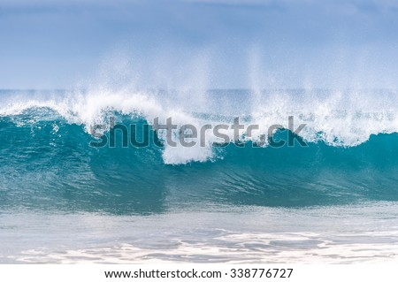 Powerful wave breaks along the shore  #338776727